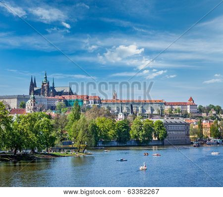 Panorama view of Vltava river and Gradchany (Prague Castle) and St. Vitus Cathedral and Charles bridge an people in paddle boats in the Prague, Czech Republic