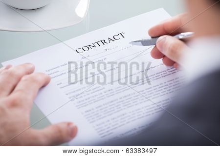 Businessperson Holding Pen On A Document
