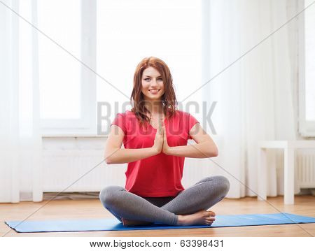 fitness, home and diet concept - smiling redhead teenager meditating at home