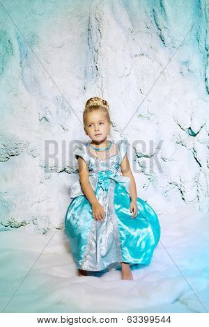 Little girl in princess dress on a background of a winter fairy tale. Baby snow queen. Sweet smiling child snowy kingdom. Kid in in carnival costume