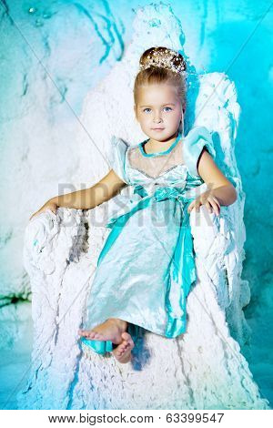 Little girl in princess dress on a background of a winter fairy tale. Baby snow queen. Sweet smiling child snowy kingdom. Kid in in carnival costume.