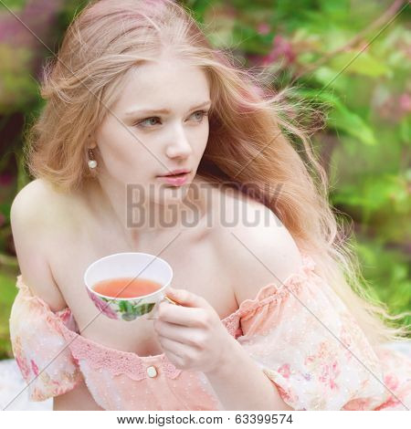 Beautiful woman with flowering tree drinking tea. Beauty young girl in garden.