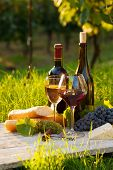 stock photo of baguette  - Two glasses of red and white wine bottle cheese and baguette - JPG