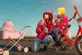 View of happy mother with her little girl  are blowing a soap bubble
