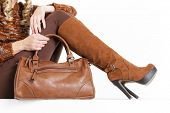 stock photo of leggins  - detail of sitting woman wearing brown clothes and boots with a handbag - JPG