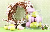 Composition with Easter eggs in glass jar and decorative wreath with blooming branches on light back