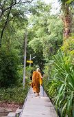 A Asian Monk Walks On The Walkway