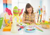 picture of thread-making  - Closeup on threads and buttons on table and young woman making easter decoration in background