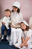 Three children posing in victorian clothes in vintage style