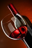 stock photo of wine-glass  - Glass and bottle of wine over red background - JPG