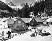 stock photo of chalet  - Trekker leaving a chalet in the mountains - JPG