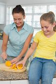 Young woman slicing oranges for daughter at kitchen counter