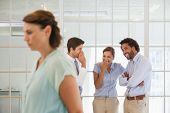foto of half-dressed  - Colleagues gossiping with sad young businesswoman in foreground at a bright office - JPG