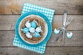 Easter eggs nest on plate over wooden background