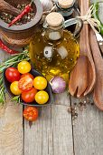 Herbs, spices and seasoning with utensils over wooden table background with copy space