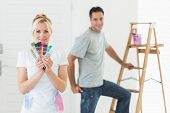 Smiling woman holding color swatches with man by ladder in a new house