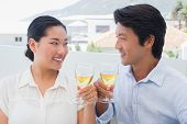 Happy couple having white wine outside on a balcony