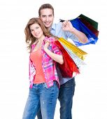 Portrait of beautiful young happy couple with colored shopping bags - isolated on white.