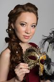 Girl holding a carnival mask. Mixed race Asian Caucasian girl.