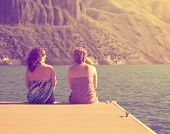stock photo of dock a lake  - two women sitting on a dock done with a retro vintage instagram filter - JPG