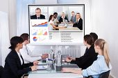 picture of video chat  - Businesspeople Sitting In A Conference Room Looking At Screen - JPG