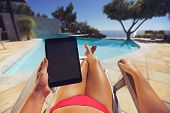 image of recliner  - Young woman relaxing on a lounge chair using a tablet PC near the pool - JPG