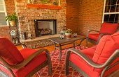 stock photo of floor covering  - Seating area around gas stone fireplace on a covered backyard deck - JPG
