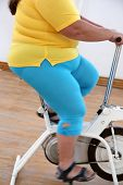 body of overweight woman exercising on bike simulator