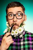 Surprised young man in glasses and a beard of flowers smoking a pipe.