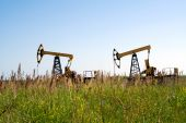 pic of nonrenewable  - Oilfield Pump Jack with a bright blue sky and clouds  - JPG