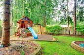 stock photo of chute  - Fenced green backyard with playground for kids - JPG