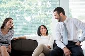 Business man smiling with female coworkers in modern environment