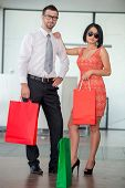 Smiling successful couple of business people with shopping bags