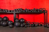 stock photo of dumbbells  - Kettlebell dumbbell and weighted slam balls weight training equipment at gym red walls - JPG