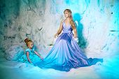 stock photo of snow queen  - Little girl with mother in princess dress on a background of a winter fairy tale - JPG