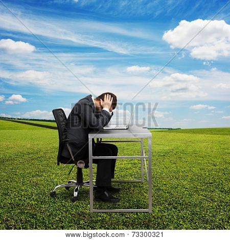 sad businessman sitting at the table with laptop and covering his head. photo at outdoor