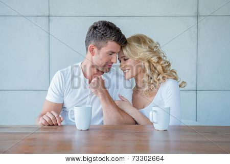Loving couple enjoying their morning coffee together sitting at a wooden counter giving each other an affectionate nuzzle