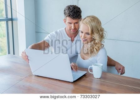 Young couple surfing the web on a laptop as they sit together at a wooden table enjoying a cup of coffee