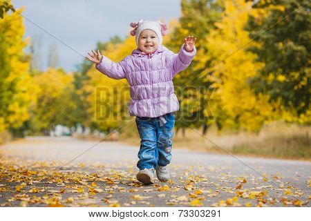 happy playful baby is running in the autumn park