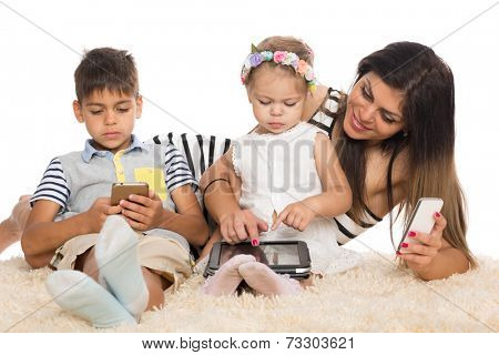 Mom and children with smartphones and tablet pc.