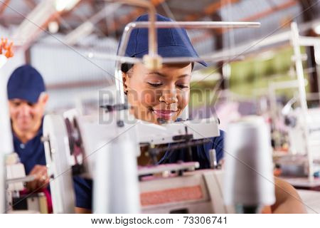 pretty african textile worker sewing with industrial sewing machine
