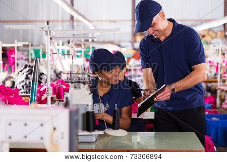 happy textile factory supervisor recording machinist performance