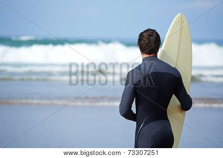 Surfer in wetsuit holding a surfboard and waiting the waves