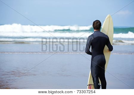 Muscular build surfer standing on the beach enjoying amazing view of ocean