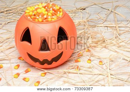 Plastic halloween pumpkin filled with candy corn on a white rustic wood table scattered with straw. Horizontal format.
