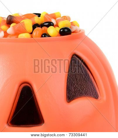 Closeup of a Halloween Jack O Lantern filled with candy corn and jelly bean candies. Square format with on a white background.