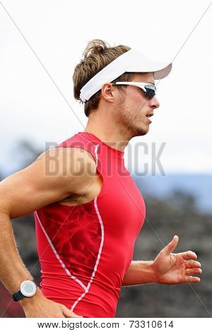 Running triathlon athlete man. Runner triathlete training for ironman wearing sports sunglasses. Young Male athlete running in red compression top.