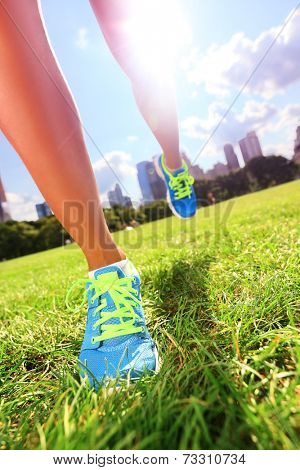Runner - running shoes closeup of woman athlete running shoes on grass. Female jogger womens shoes in Central Park, New York City.