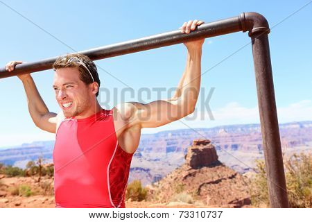 Exercising Fitness athlete man training pull ups in amazing nature landscape of Grand Canyon. Strength training fit male working out exercising outdoors in summer doing pull-ups and chin-ups.