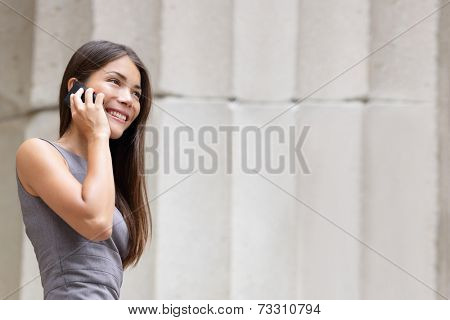 Business woman lawyer talking on smartphone outside. Successful young multiracial Caucasian / Asian Chinese professional woman.